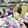 (Brad Davis/The Register-Herald) Chirstina Cowley (right), and AmeriCorps Vista working with the United Way of Southern West Virginia, helps Nine-year-old Malia Anderson (2nd from right), 10-year-old Jaylon Walton (back turned), 9-year-old Janiyah Towles (2nd from left), 9-year-old Lyric Walton (far left) and several other youngsters not photographed in making wind chimes out of paper cups and beads at the kids corner during Fridays in the Park yesterday afternoon.