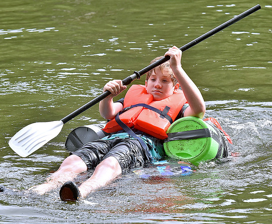 """(Brad Davis/The Register-Herald) Will Lindberg's homemade boat design consisted of a body board, three empty buckets and a ton of duct tape, and it worked during the """"If It Can Float' portion of the Alderson Canoe Races Sunday afternoon as part of the town's 4th of July Celebration."""