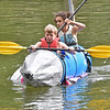 "(Brad Davis/The Register-Herald) 13-year-olds Autumn Middlebrook and Bryce Thompson successfully complete two laps in there homemade boat during the ""If It Can Float' portion of the Alderson Canoe Races Sunday afternoon as part of the town's 4th of July Celebration."