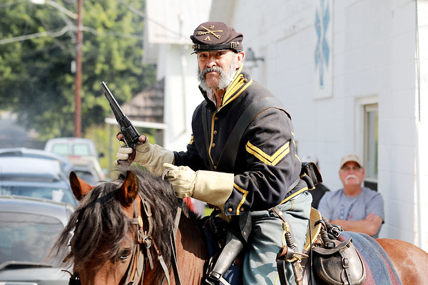 Civil War re-enactor portraying a Federal Army cavalry member turns his horse after return fire to the local Home Guard infantry during a battle as part of Monroe County Heritage Day in Union on Saturday.  (Chris Jackson/The Register-Herald)