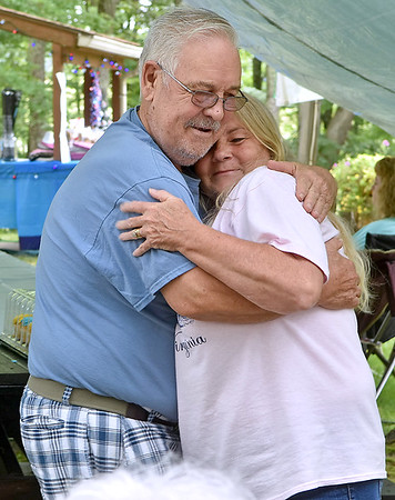 (Brad Davis/The Register-Herald) Beckley resident Joyce Lilly, now Whitt through marriage, gets a big hug from fellow Beckley resident Robert Earl Lilly as the two enjoy a day a family and friends during the annual Lilly Family Reunion Saturday afternoon near Ghent.