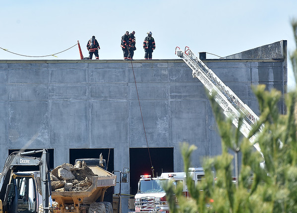 (Brad Davis/The Register-Herald) Beckley firefighters put out the last remnants of a fire that broke out briefly on the roof of a building under construction in the Pinecrest Industrial Park Friday afternoon. Construction workers on scene said they were installing roofing materials when static electricity ignited some of the material, said to be an adhesive, used in the process. Workers on scene reported no injuries. The building will be the new Dr. Pepper location when completed, which is currently located on Robert C. Byrd drive in Prosperity.