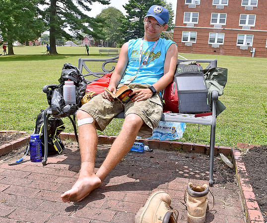 (Brad Davis/The Register-Herald) Troop 2320 (Cincinnati, Ohio) Scout David Duckett notices the camera as he tries to relax with a book after a long morning of manual labor on the grounds of Jackie Withrow Hospital Thursday afternoon in Beckley.