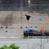 A bird is caught in the frame as workers continue work on the Bluestone Dam Wednesday in Hinton. (Chris Jackson/The Register-Herald)