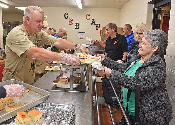 (Brad Davis/The Register-Herald) Winfield resident Cathy Kelley, right, gets a plate of steamed ramps and other hot food from volunteer Mike Cooper during the Feast of the Ramson, a nationally-renowned ramp feast Saturday afternoon in Richwood. Kelley, who came all the way from the Charleston area for the event, was awaiting the arrival of her son Brian from San Diego, California via Pittsburgh.