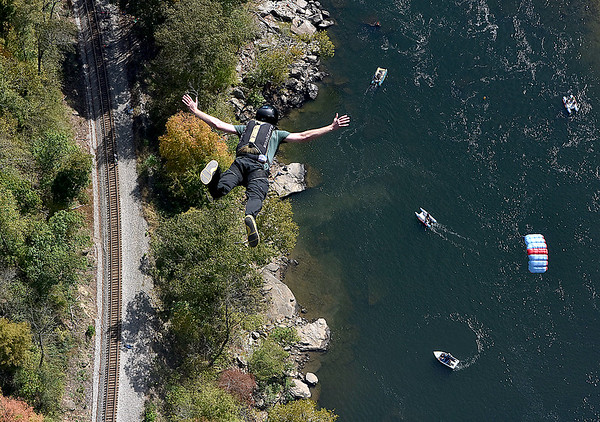 (Brad Davis/The Register-Herald) A B.A.S.E. jumper freefalls during Bridge Day Saturday afternoon.