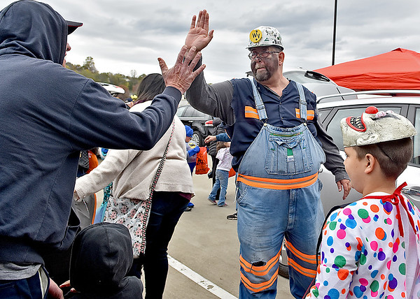 (Brad Davis/The Register-Herald) West Virginia Miners mascot Big Paul greets trick or treaters with big high-fives as they make their way into Tailgate Halloween Saturday afternoon atop Beckley's Intermodal Gateway.