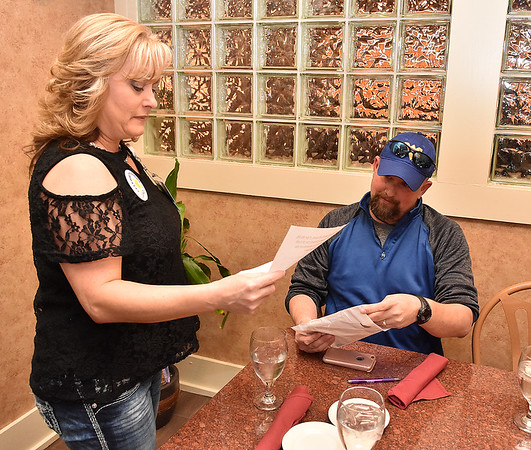 (Brad Davis/The Register-Herald) RGH's Sherri Sears brings a prize packet over to to James Shufflebarger, one of the evening's first prize winners during Clebrity Night at Pasquale's May 8.