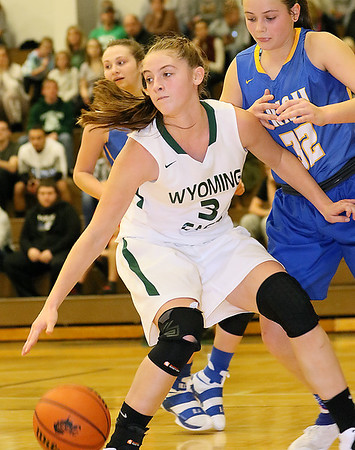 (Brad Davis/The Register-Herald) Wyoming East's Kara Sandy is forced to turn out of a drive to the basket to look for an open teammate as St. Joeseph Central's Paige Shy applies tough defense during the Lady Warriors' win over the Irish Friday night in New Richmond.