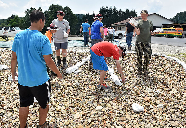 """(Brad Davis/The Register-Herald) Scouts from multiple troops out of Illinois place the letters """"RCSWA"""" with painted rocks as part of a landscaping project at the Raleigh County Solid Waste Authority Thursday afternoon in Beckley."""