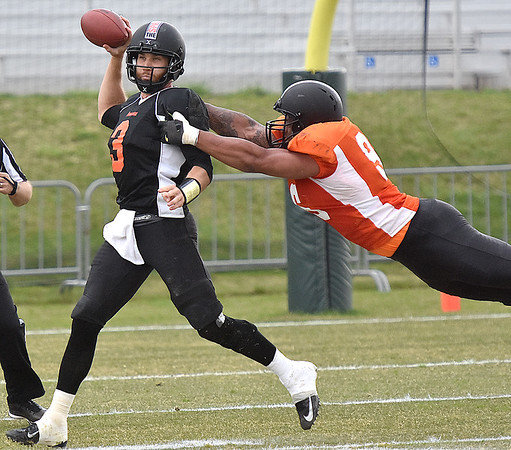 (Brad Davis/The Register-Herald) West (black jerseys) quarterback McLeod Bethel-Thompson is flushed from the pocket by East (orange jerseys) pass rusher Patrick McNeil during the opening game of The Spring League Saturday afternoon in White Sulphur Springs.