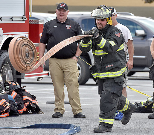 (Brad Davis/The Register-Herald) Rhodell Volunteer Firefighter Fred Shrewsbury deploys, assembles and uses a fire hose as quickly as possible during the obstacle course portion of a Raleigh County Firefighter Day event geared towards a mixture of showcasing firefighter tactics and attracting needed volunteers to several departments around the county Sunday afternoon at the Crossroads Mall.