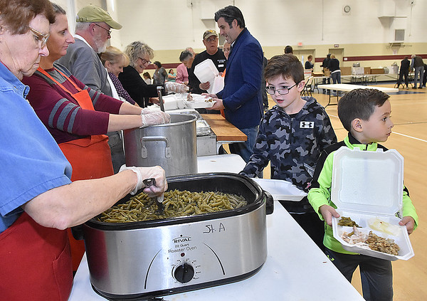 (Brad Davis/The Register-Herald) Youngsters Harper Phillips (far right), 6, and Gabriel Crist, 7, fill up their to-go boxes during Lewis Christian Community Center's Thanksgiving dinner Thursday afternoon in Oak Hill.