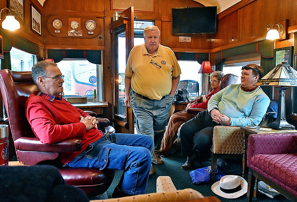 (Brad Davis/The Register-Herald) Nelson McGahee (standing), co-owner of The Dearing, a restored, 1920's era passenger car, makes his way inside as New River Train Excursion riders (from left) Danny Neal of Milton, his wife Marion and Raleigh, North Carolina resident John Schneider relax beofre the return trip to Huntington during Hinton Railroad Days Sunday afternoon.