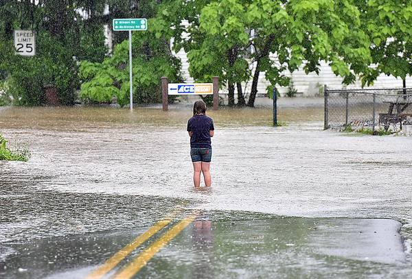 (Brad Davis/The Register-Herald) Nine-year-old Minden resident Teresa Sharp looks out towards flooding at the intersections of Minden and McKinney Roads as the rain continues to fall into Monday afternoon.