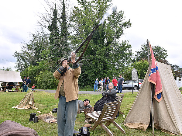 (Brad Davis/The Register-Herald) Civil War re-enactor Rick Henry fires his weapon as fellow reenactors Time Greene and Anita Henry look on from tehi encampment during Founder's Day ceremonies Saturday.