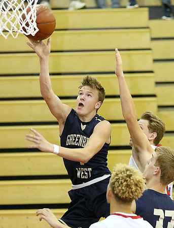 (Brad Davis/The Register-Herald) Greenbrier West's Noah Midkiff drives hard to the basket as Independence defender Logan Stump defends Friday night in Coal City.