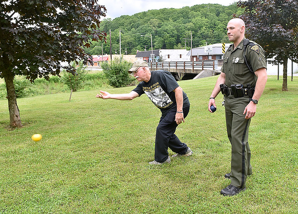 (Brad Davis/The Register-Herald) Veteran Neal Holliday, second from right, takes on State Trooper J.C. Teubert in a game of Murbles during a tournament between veterans and first responders as part of the West Virginia Veterans Reunion in Rainelle Sunday afternoon.