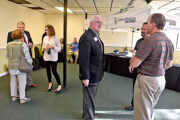 (Brad Davis/The Register-Herald) Mayor Rob Rappold, middle, arrives and greets WVVA-TV6's Keith Vonscio, right, and BJW Printing's Randy Thompson (hidden behind Vonscio) during the opening moments of this month's Chamber Business After Hours at Custom Business Solutions' new location off Ontario Drive in Mount Hope Thursday evening. The business's owners, Gordie Roop and Tiffany Kapp mingle at left.