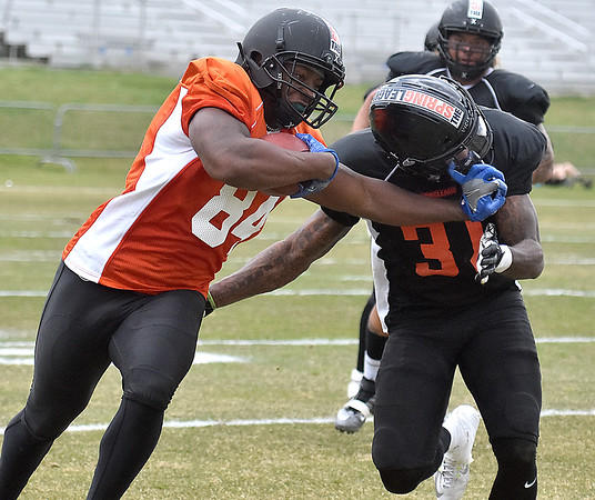(Brad Davis/The Register-Herald) East (orange jerseys) tight end Manasseh Garner stiff-arms West (black jerseys) safety Joshua Furman after making a catch during the opening game of The Spring League Saturday afternoon in White Sulphur Springs.