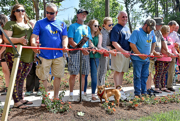 (Brad Davis/The Register-Herald) Family and friends of the late Belinda Scott, including husband Ronnie (3rd from left) and their dog Dancer, line up to cut the ribbon opening Belinda's Honeybee Garden, a special memorial to her inside the new Brad Paisley Park Friday afternoon.
