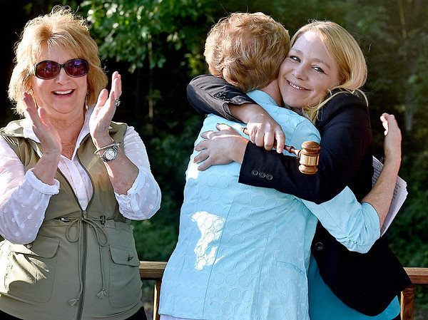 (Brad Davis/The Register-Herald) Paige Powers (right), the new President of the Beckley Board of Realtors, gets a big hug from emcee and 2017 West Virginia Association of Realtors President Glenna Swiger after receiving the ceremonial gavel as outgoing president Kay Booth (left) applauds during the conclusion of the board's annual installment of new officers Thursday evening at Daniel Vineyards.