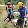 (Brad Davis/The Register-Herald) Girls scout Alison Isbell is caught by worker Spencer Horn on the the landing tower of one of the zip lines at the Girl Scout Jamboree Saturday afternoon at the Bechtel Summit Reserve.