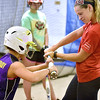 (Brad Davis/The Register-Herald) Young softball player Brylee McGrady gets hands-on coaching on how to generate the most strength with proper swing mechanics as she tries to push back on the bat of former Marshall University and current Team USA softball player Morgan Zerkle, left, during a special clinic at the Full Count Baseball and Softball Academy Saturday afternoon in Oak Hill.