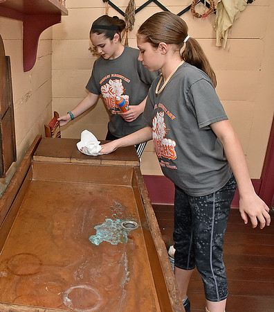 (Brad Davis/The Register-Herald) Bradley Elementary 5th graders and student council members Mia Houck, near, and partner Sarah Hopkins clean in the kitchen area of Wildwood House, the home Beckley founder Alfred Beckley, during a Spring cleanup Saturday afternoon.