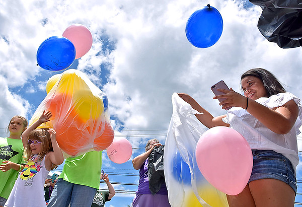 (Brad Davis/The Register-Herald) Youngsters release hundreds of balloons into the air, many with special messages written on them in memory of friends and loved ones lost in last year's flooding, during a family fair in the Old White Motors parking lot Saturday afternoon in White Sulphur Springs.