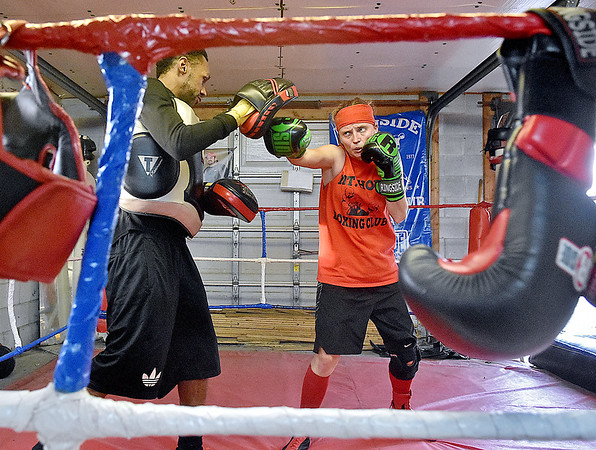 (Brad Davis/The Register-Herald) Toughman Contest fighter Amber Sweeney, the 2013 Beckley runner-up and champion of this year's Huntington event in January, trains with two-time past Toughman champion Charles Moore Monday evening at the Mount Hope Boxing Club. Sweeney, like many fighters with serious ambitions of taking home a title, has been training with Carl Murdock three days a week to get ready for a tough division that features last year's champ Sarah Coffey.