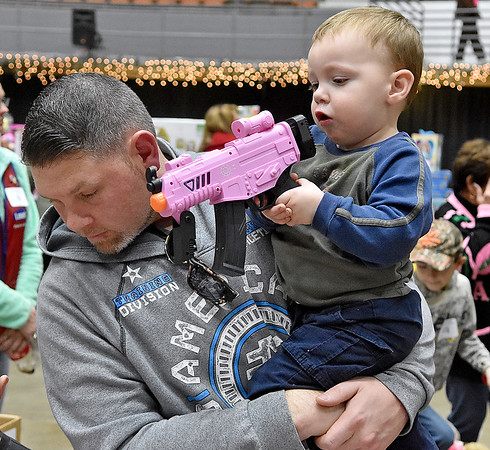 (Brad Davis/The Register-Herald) Two-year-old Ian Reed checks out a toy as dad Harley looks on during the annual Mac's Toy Fund event Saturday morning at the Beckley-Raleigh County Convention Center.