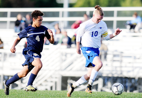 Independence's Sean Salmons(10) makes a run past Shady Spring's (4) towards goal during the soccer match Thursday in Beckley.  Salmons scored on the run. (Chris Jackson/The Register-Herald)