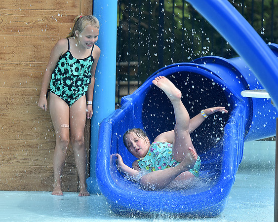 (Brad Davis/The Register-Herald) 8-year-old Brailynn McCarty, left, gets a laugh out of 7-year-old Jaycee Wooten as she races down one of the slides inside the Splash Park at Lake Stephens Saturday afternoon.
