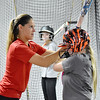 (Brad Davis/The Register-Herald) Young Fayetteville softball player Annie Johnson gets hands-on coaching on her batting skills from former Marshall University and current Team USA softball player Morgan Zerkle, left, during a special clinic at the Full Count Baseball and Softball Academy Saturday afternoon in Oak Hill.