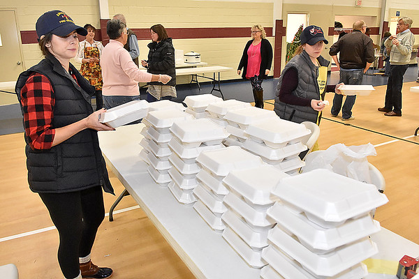 (Brad Davis/The Register-Herald) Volunteers Courtney Crist-Phillips, left, and sister Lynsey Crist (holding box at right) stack to-go meals of turkey, mashed potatoes, green beans and more for deliveries and carry-outs to those who came to Lewis Christian Community Center's Thanksgiving dinner Thursday afternoon in Oak Hill. Volunteers said at least around 1,500 meals were delivered throughout the community while many more were served on site throughout the day.