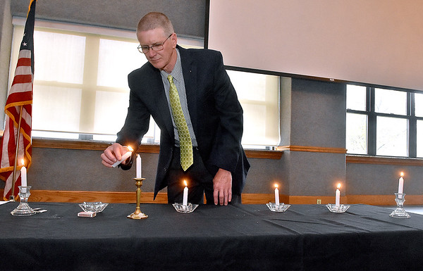 (Brad Davis/The Register-Herald) Tom Sopher lights the seventh candle in memory of over 5 million non-Jews killed in concentration camps during World War II and in acknowledgement of other genocides around the world past and present during Yom HaShoah Sunday afternoon inside WVU Tech's Carter Hall. The other six candles each represent a million souls lost during the holocaust.