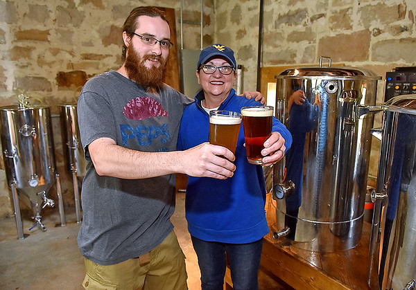 (Brad Davis/The Register-Herald) Dobra Zupas resident brewer Rebecca Zupanick and chef/brewer John Lester offer cheers as they show off their Hopped Up I.P.A (right). and Wyco Wheat, brews they will be taking to the first ever West Virginia Craft Brew Festival Saturday, April 29 at the State Fairgrounds in Fairlea.