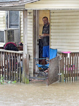 (Brad Davis/The Register-Herald) Minden resident Darrell Sharp looks out his door as he and his family wait out the rain and flood waters surrounding their Minden Road home Monday afternoon.