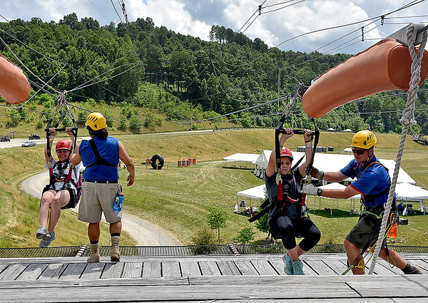 "(Brad Davis/The Register-Herald) New York girl scout Kaytlyn Ashcroft, right, is caught by landing worker Spencer Horn and Maine girl scout Colleen Grant is caught by Ihell ""Panda"" Palermo as they take run down a zip line at the Girl Scout Jamboree Saturday afternoon at the Bechtel Summit Reserve."