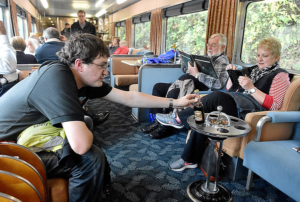 (Brad Davis/The Register-Herald) New River Train worker Ethan Peake, left, reaches for his soda as he relaxes on break inside one of the silver class cars while excursion riders Cindi and Dennis Tinseth (right) of Charlotte, North Carolina relax as well during Hinton Railroad Days Sunday afternoon.