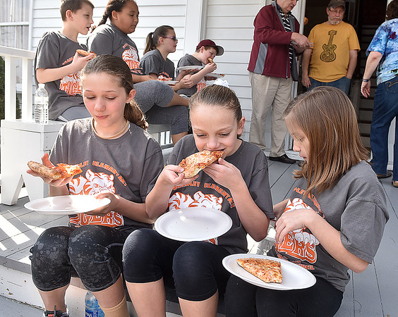 (Brad Davis/The Register-Herald) Bradley Elementary 5th graders (from left) Mia Houck, Kylie Norris and Lainey Pack join the rest of their fellow student council members in chowing down on some pizza as they fuel up prior to a Spring cleanup at Wildwood House Museum Saturday afternoon.
