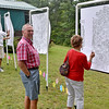 (Brad Davis/The Register-Herald) Jim Bowling, left, looks on as Barbara Halstead, whose grandmother was a Lilly, looks over one of several family trees on display during the annual Lilly Family Reunion Saturday afternoon near Ghent.