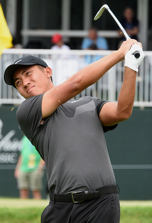 C.T. Pan hits his tee shot on the 18th hole during the first round of The Greenbrier Classic. Watching to the left is Michael Kim.<br /> (Rick Barbero/The Register-Herald.com