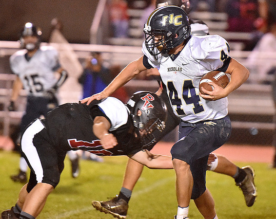 (Brad Davis/The Register-Herald) Nicholas County's D.J. McCutcheon carries the ball as PikeView defender Ethan Begovich tries to make a tackle Friday night in Gardner.