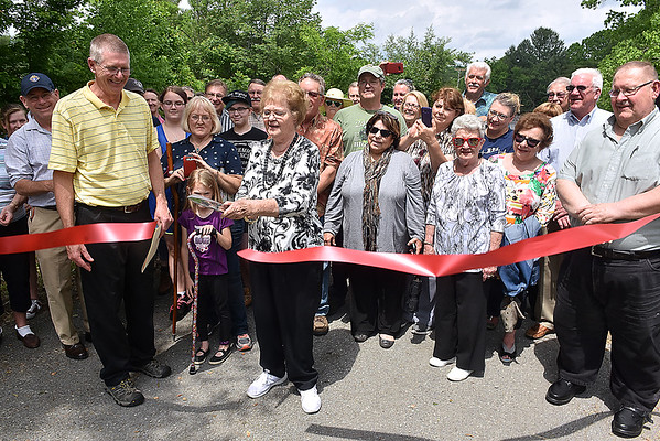 (Brad Davis/The Register-Herald) June Truax, far left, the 3rd Great Granddaughter of Alfred Beckley, cuts the ceremonial ribbon opening up the trail to the Beckley Mill site Saturday afternoon.