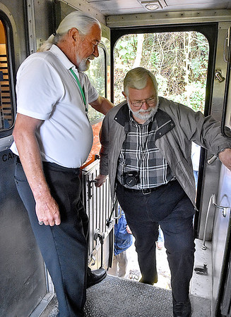 (Brad Davis/The Register-Herald) Rick Fox, left, a server on one of the New River Train's silver class cars, helps and greets excursioneers as they climb back onto the train during Hinton Railroad Days Sunday afternoon.