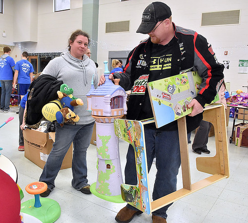 (Brad Davis/The Register-Herald) Saulsville residents Jessica and Terry Hill come away with exactly the gifts they came to find as they head for the exit during the Wyoming County Toy Fund Sunday morning at Wyoming East High School. The two showed up to begin waiting for the event to begin at 4:00 a.m.