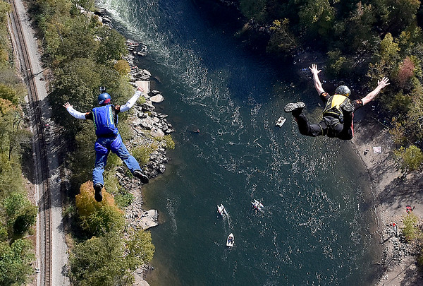 (Brad Davis/The Register-Herald) A pair of B.A.S.E. jumpers fall to earth during Bridge Day Saturday afternoon.