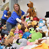 (Brad Davis/The Register-Herald) Volunteer Karen Haynes climbs a mountain of stuffed animals to find the right one for a customer during the Wyoming County Toy Fund Sunday morning at Wyoming East High School.